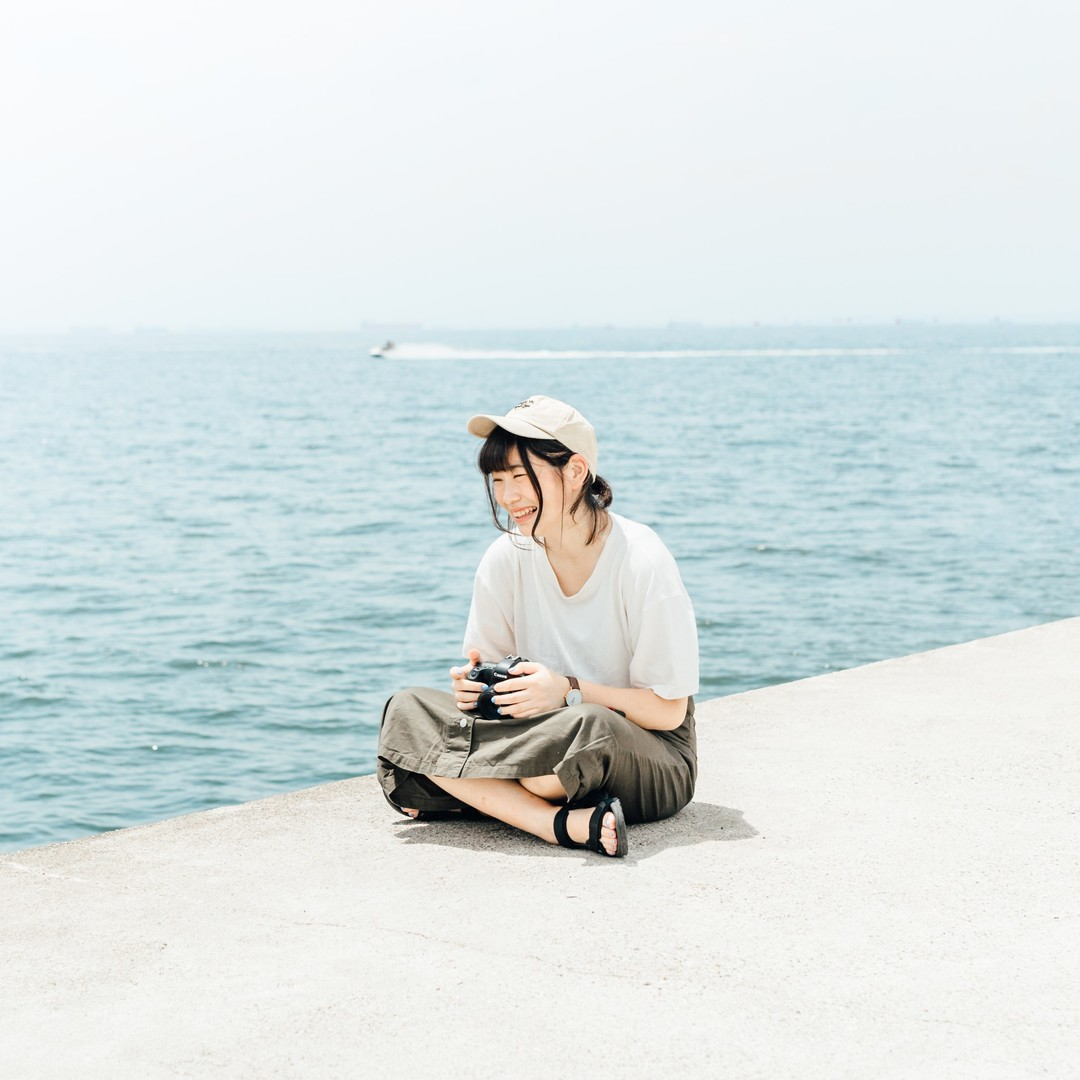 海辺の堤防に座る女性